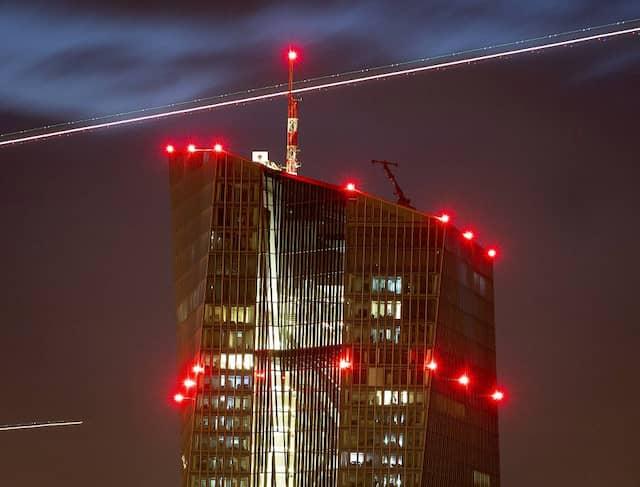 An der Europäischen Zentralbank in Frankfurt leuchten rote Warnlampen, im Hintergrund ziehen Flugzeuge Lichtspuren.