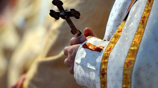 Ein Bischof hält während einer katholischen Messe ein Kreuz in den Händen (Archivbild).