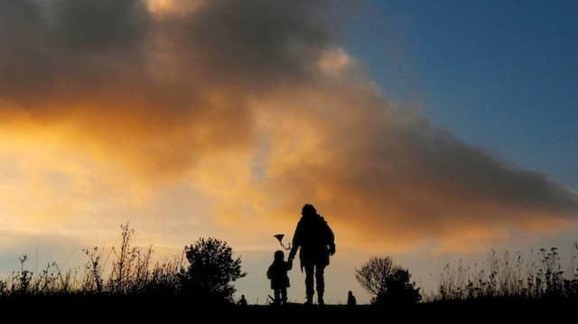 Eine Mutter geht mit ihrem Kind über einen Feldweg spazieren.