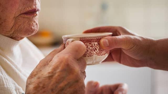 Eine Pflegerin aus Polen reicht eine alten Dame die Kaffeetasse.