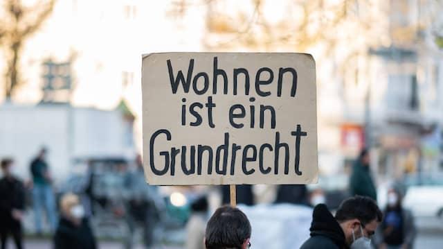 """Ein Mann hält während einer Kundgebung zum Urteil Bundesverfassungsgerichts zum Berliner Mietendeckel ein Schild: """"Wohnen ist ein Grundrecht""""."""