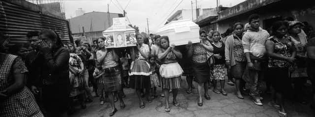 Bewohner tragen Särge mit verstorbenen Angehörigen in Richtung Friedhof von San Juan Alotenango.
