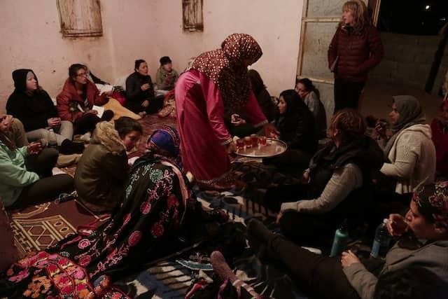 Touristinnen und Beduininnen des Hamada-Stamms lassen sich von Umm Yasser in ihrem Haus mit heißem Tee bewirten.