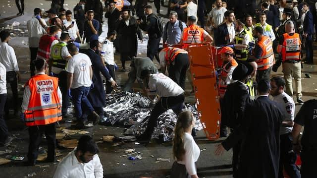 Rettungskräfte stehen bei den abgedeckten Körpern von Opfern der Massenpanik.