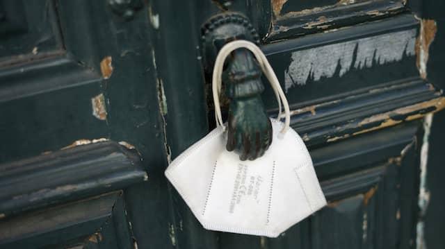 Eine Maske an einer Tür in Lissabon: Die meisten Portugiesen sind auch durch eine Impfung geschützt.