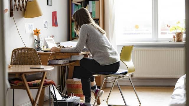 Eine junge Frau arbeitet in ihrer Wohnung.