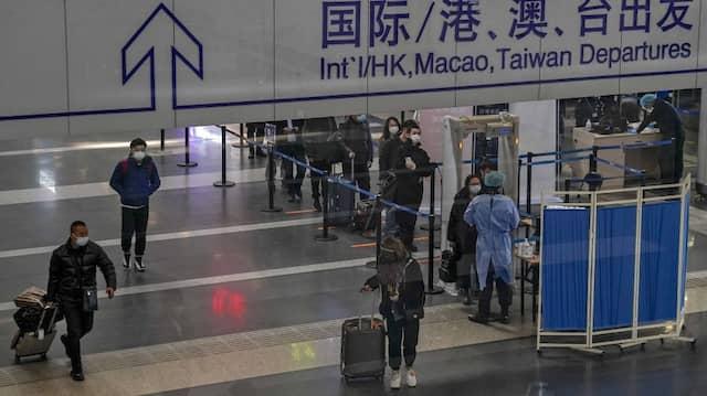 Passagiere stellen sich in der Abflughalle des Flughafens Peking zur Temperaturkontrolle an.