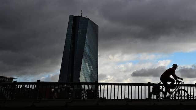 Während dunkle Regenwolken über die Stadt hinwegziehen, fährt ein Radfahrer unweit der Europäischen Zentralbank (EZB) über die Flößerbrücke.