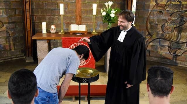 Pfarrer Sven Engel von der Darmstädter Matthäusgemeinde tauft im Mai 2016 in seiner Kirche einen Flüchtling (nachgestellte Szene).