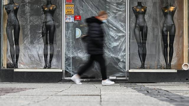 Eine Frau geht Anfang Januar in der Frankfurter Innenstadt an einem geschlossenen Laden vorbei.