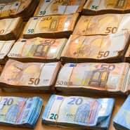 Geldbündel liegen auf einem Tisch.