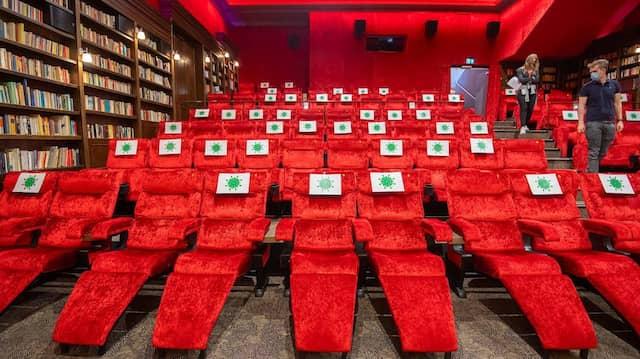 Hannover: Einzelne Sitzplätze in einem Kinosaal vom Kino Astor Grand Cinema sind mit Zetteln mit aufgedrucktem angedeuteten Virus-Symbol abgesperrt, damit Kino-Besucher einen Abstand von 1,5 Meter zueinander einhalten können.