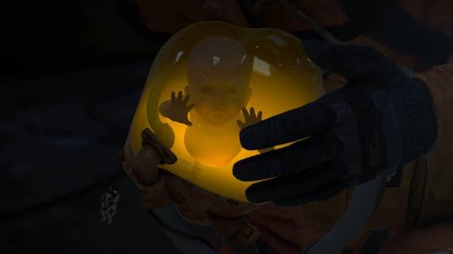 """Adoptierte Lebensversicherung: In """"Death Stranding"""" führt dieser kleine Kerl im Glas den Spieler sicher durch die Landschaft."""