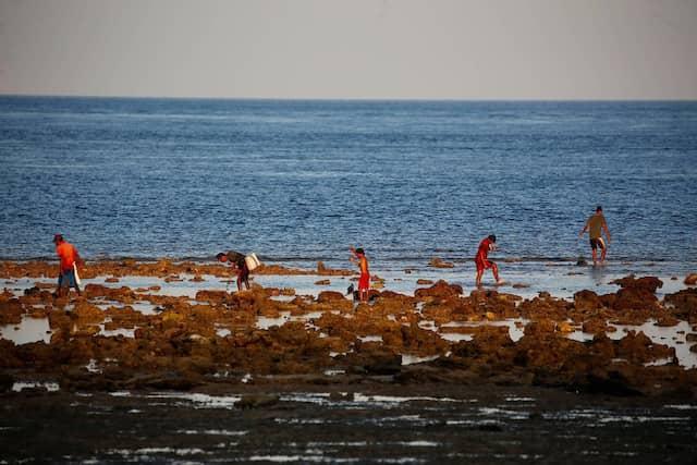 Der Bauer Ndelu Ndaha geht mit seinem Sohn Dimas Mbaha Konda Lura und Ndahas Freunden am Strand von Puru Kambera angeln.
