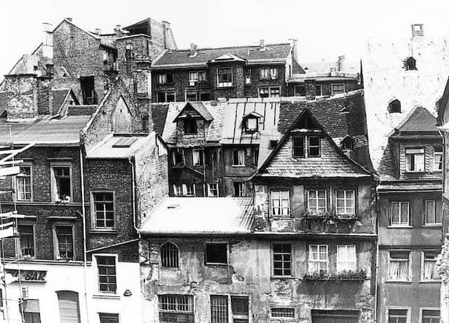 """Rotekopfgasse – Blick vom Gutenberg Museum in Richtung Rheinstraße, um 1962, vor der Altstadtsanierung. Im Vordergrund die noch nicht sanierten Häuser der Rotekopfgasse. Im Hintergrund sieht man Teile der Fischergasse, links unten die Bar """"KC"""" (Kleines Casino), damals sehr beliebt bei den GI's."""