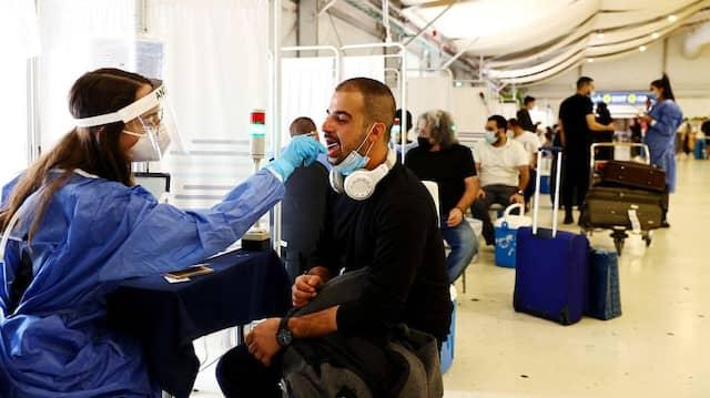 Eine Frau nimmt einem Mann am Flughafen in Tel Aviv einen Abstrich ab, um ihn auf das Coronavirus zu testen.