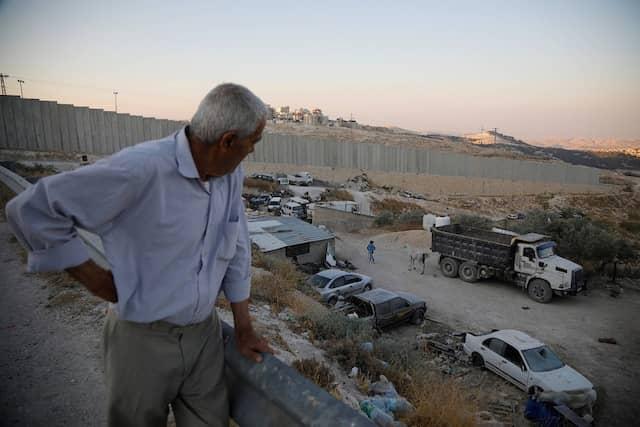 """Der 74-jährige Palästinenser Ali Farun steht an der Mauer, die Al-Eizariya und die Siedlung Maale Adumim (Hintergrund) im besetzten Westjordanland trennt. """"Es spielt keine Rolle, ob das Jordantal annektiert wird, oder besetzt bleibt - es bleibt so oder so unter ihrer Kontrolle""""."""