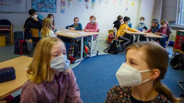 Schüler einer vierten Klasse sitzen im Unterricht an der Grundschule Russee in Kiel zusammen an einem Tisch und tragen dabei einen Mund-Nasen-Schutz.