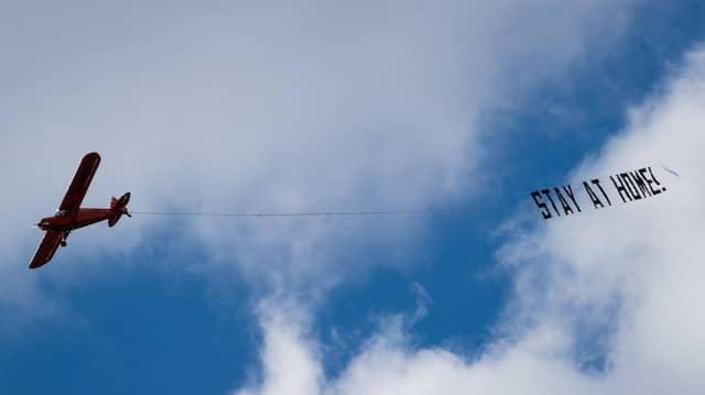 Ein Flugzeug fliegt am 21. März 2020 mit einem Banner über Hamburgs Innenstadt.