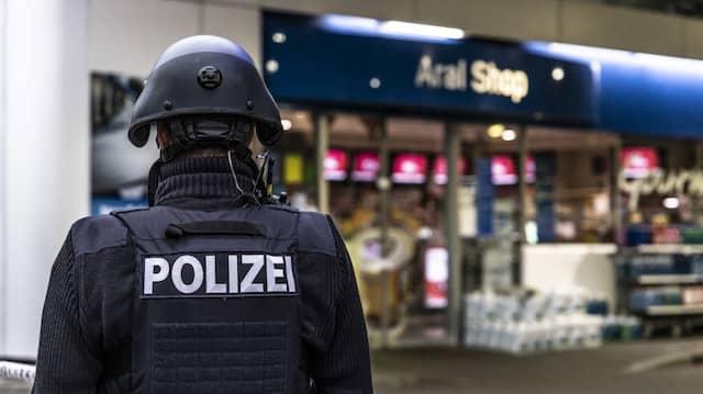 Ein Polizist sichert am frühen Sonntagmorgen die Tankstelle in Idar-Oberstein.