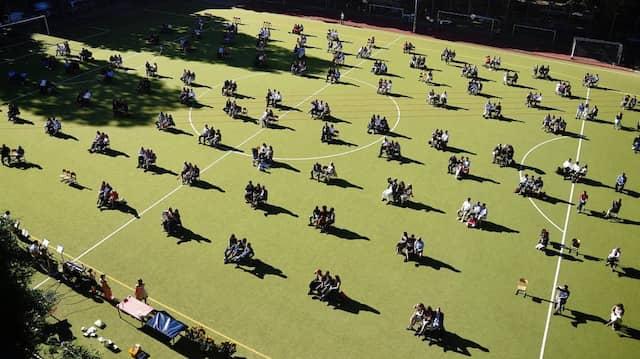 Auf einem Sportplatz versammeln sich die Abiturienten des Jahrgangs 2021 mit ihren Angehörigen für die Zeugnisvergabe