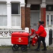 Eine Mitarbeiterin der britischen Post stellt in London Post zu. Wegen der Corona-Pandemie kann sie in 28 Gegenden kaum noch Briefe und Pakete ausliefern.