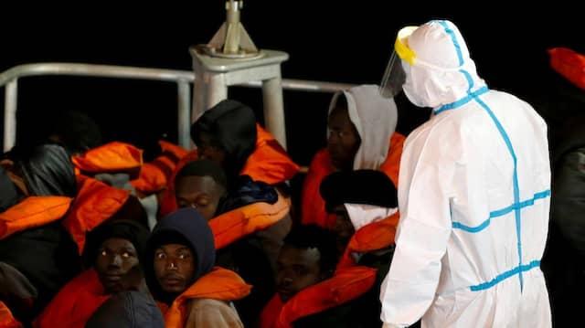 Von einem Militärschiff gerettete Migranten kommen am 10. April in Malta an, wo sie von Soldaten in Empfang genommen werden, die wegen der Covid-19-Pandemie Schutzkleidung tragen.