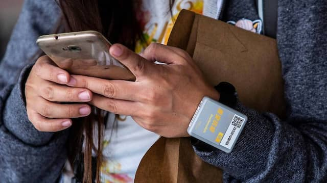 Flugpassagierin mit Handy und Corona-Tracking-Armband in Hongkong