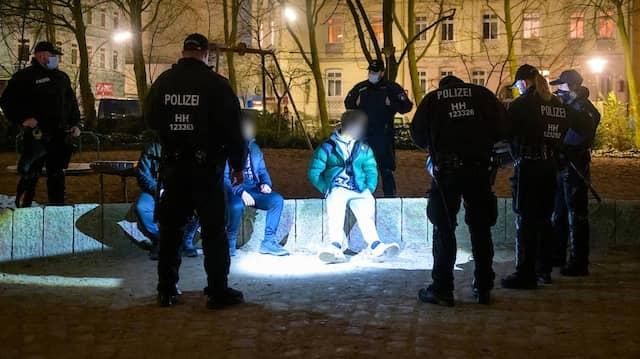 Drei junge Männer werden am Donnerstag in Hamburg auf einem Spielplatz von der Polizei kontrolliert.