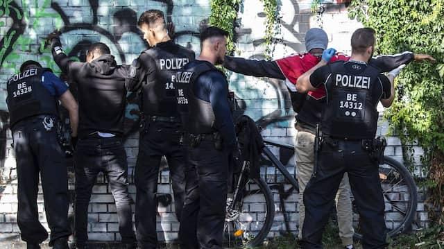 Kontrollen am Brennpunkt: Polizisten durchsuchen zwei Männer am Görlitzer Park in Berlin.