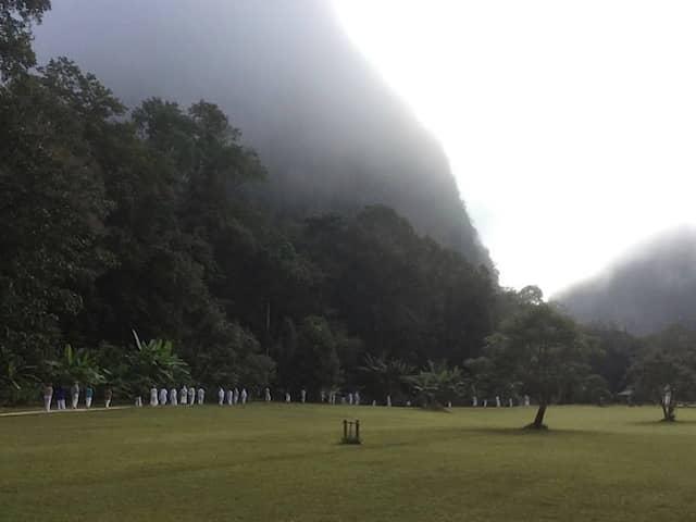 Auch gehen ist Meditation: Weißgewandete Gäste im üppigen Grün des Tals.