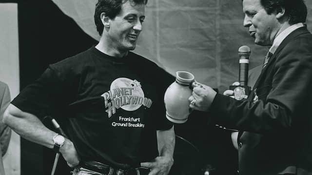Schobbepetzer: Sylvester Stallone (links) bekommt bei der Grundsteinlegung für ein Planet Hollywood Restaurant in Frankfurt einen Bembel von Ordnungsdezernent Udo Corts.