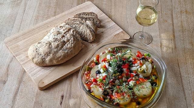 Heimischer Klassiker zur Linderung von Fernweh: Mediterraner Handkäs' mit Silvanerbrot und einem Glas Weißwein.