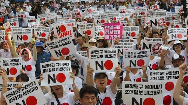 """Demonstranten mit Schildern mit der Aufschrift """"Wir verurteilen den japanischen Premierminister Shinzo Abe"""""""