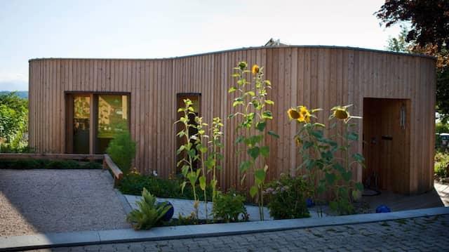 Freundliche Rundungen und Flachdach: Zwischen Häusern mit Satteldach und Putzfassade sticht das kleine, kellerlose Haus hervor