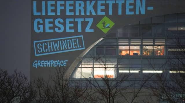 Bei einer Greenpeace-Aktion zum Lieferkettengesetz wird am frühen Morgen der Spruch «Lieferkettengesetz. Schwindel» an die Außenfassade des Bundeskanzleramts projiziert, 16. Februar 2021.