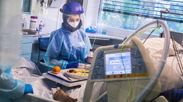 Auf der Intensivstation des Asklepios Klinikums Langen bringen Pflegerinnen in Schutzkleidung einem Corona-Patienten eine Mahlzeit.