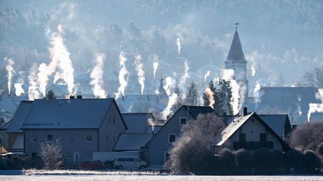 Schornsteine auf den Dächern der Häuser rauchen in der kalten Luft im bayerischen Luthe-Wildenau.
