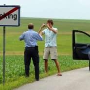 """Beliebt bei Touristen: Ein Mann posiert vor dem Ortsausgangsschild von """"Fucking"""""""