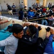 Protestierende Iraker versuchen, in Bagdad eine Betonmauer umzustürzen.