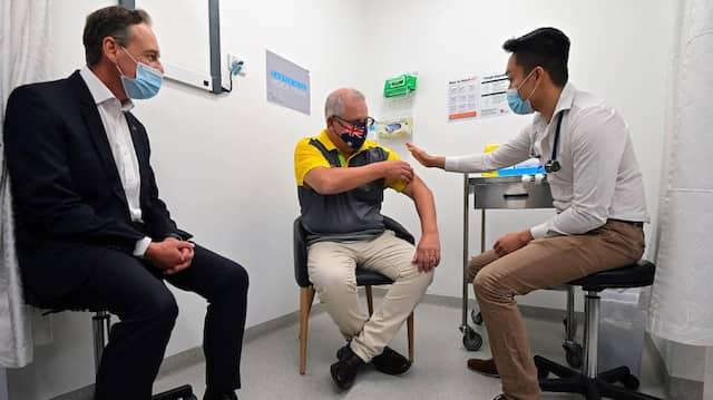 Der australische Gesundheitsminister Greg Hunt beobachtet im Februar 2021, wie Premierminister Scott Morrison mit dem Vakzin von Biontech/Pfizer geimpft wird.
