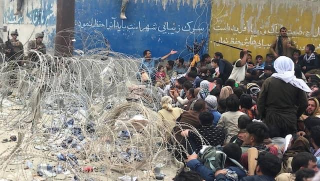 """Die ausländischen Streitkräfte errichteten eine Barriere aus Stacheldraht, um die Menschen vom Flughafen fernzuhalten. Auf der Seite der Einwohner halten Mitglieder der """"Einheit 01"""" (wie sie von den Leuten genannt wird) die Menschen auf ihren Plätzen, manchmal durch Schüsse in die Luft, manchmal mit einem Schlagstock."""