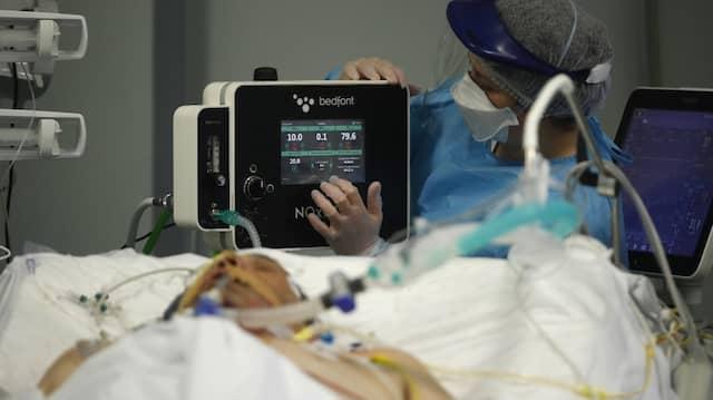 Ein Mitarbeiter des Gesundheitswesens versorgt einen Patienten in der Corona-Intensivstation eines Krankenhauses.
