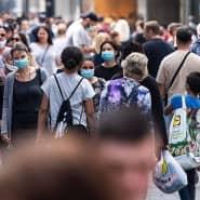 Zahlreiche Menschen mit Masken sind vergangenen Mai in Köln unterwegs.