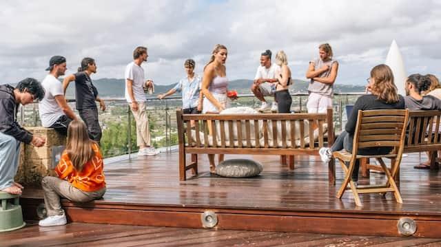Ein Bild wie ein Gemälde: Influencer und Crew reden auf der Terrasse der Villa