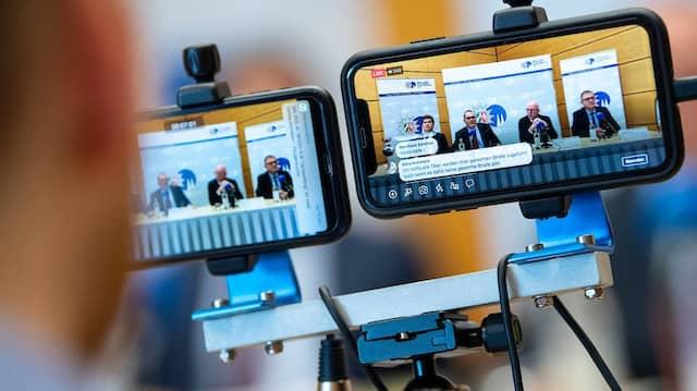 Bergisch Gladbach: Ein Mitarbeiter der Kölner Polizei streamt die Pressekonferenz mit zwei Mobiltelefonen ins Internet.