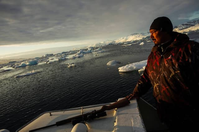 Sonnenlicht scheint auf das Gesicht des Robbenjägers Henrik Josvasson. Die traditionelle Jagd wird in Grönland immer schwieriger. Er gehört zu den letzten Robbenfängern von Tasiilaq.