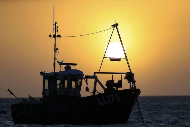 Sonnenaufgang hinter einem Fischerboot.