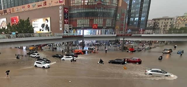 Fahrzeuge stehen in Zhengzhou in der zentralchinesischen Provinz Henan am Dienstag auf einer überfluteten Straße.