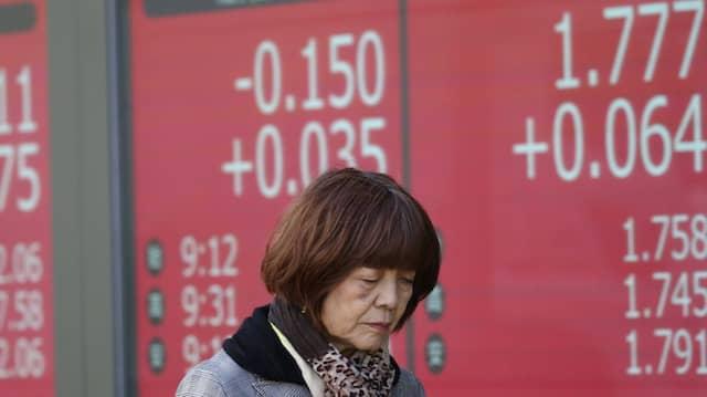 Eine Passantin läuft an einer elektronischen Anzeige der neuesten Indizes der Tokioter Börse vorbei.